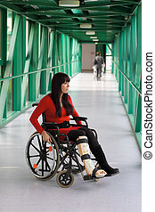 Woman with leg in plaster and wheelchair in the hospital -...