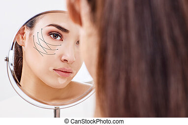Woman with lifting arrows on face looking in the mirror.