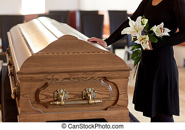 woman with lily flowers and coffin at funeral - people and...