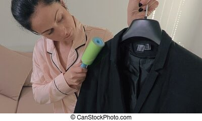 Woman with lint roller cleaning jacket
