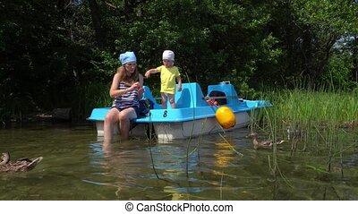 Woman with little boy feeding ducks birds sitting on catamaran near wild lake