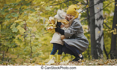 Woman with little daughter in autumn park