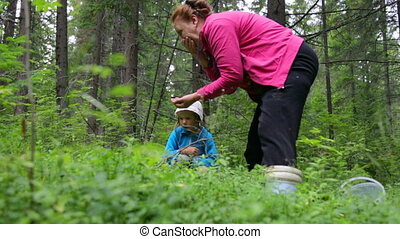 Woman with little girl gathering berries in forest