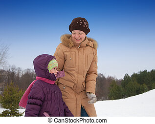 Woman with little girl in winter