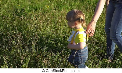 Woman with little girl is walking along the green grass.