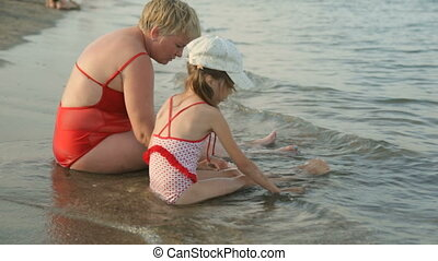 Woman with little girl on beach