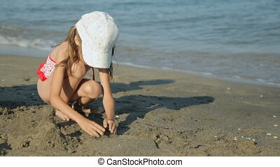 Woman with little girl playing with sand on beach