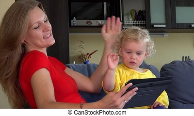 woman with little girl waving hands looking at tablet computer.