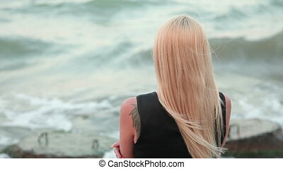 woman with long blond hair looking at the sea