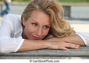 Woman with long blonde hair leaning on a bench