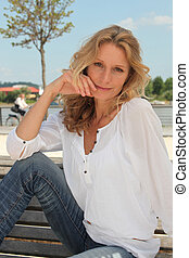 Woman with long blonde hair sitting on a bench