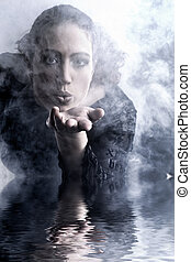 Woman with long curly hair blowing smoke