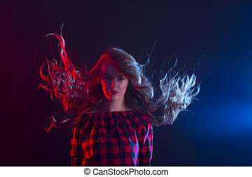 Woman with long curly hair in motion at studio