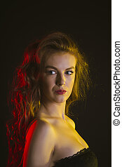 Woman with long curly hair in the dark