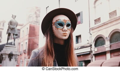 Woman with long hair and hat wearing a white carnival face...