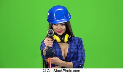 Woman with long hair in a plaid shirt holding a drill and drills it on a green background