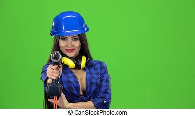Woman with long hair in a plaid shirt holding a screwdriver and drill them on a green background