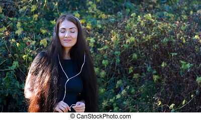Woman with long hair in headphones listening music on a...