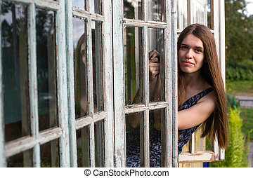 Woman with long hair looks from of the window of the veranda.