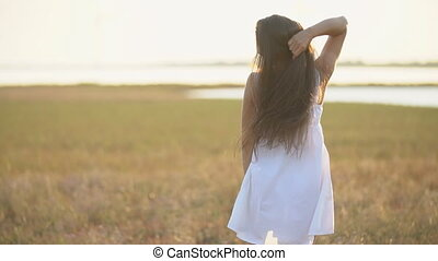 woman with long hair walking in nature