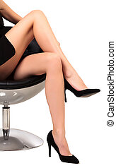 Woman with long legs sitting in a chair, isolated on white background