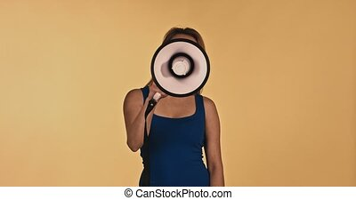 Woman with loudspeaker on yellow background - Woman with...