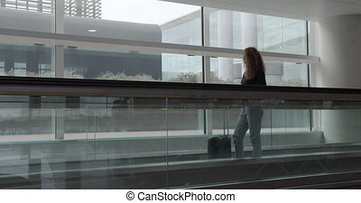 Woman with luggage a stands on the escalator and looks around at the airport.