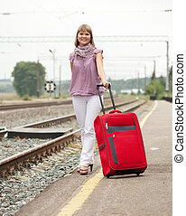 woman with luggage   on  railroad
