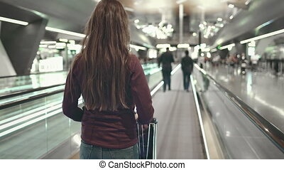 woman with luggage stand on speedwalk at airport