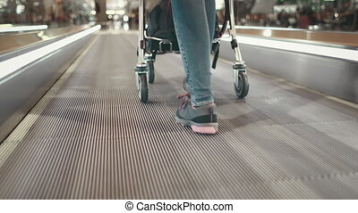 Woman with Luggage Truck Walk at Airport Terminal. Tracking Shot of Girl Legs Cart Wheel Close up. Passenger Pushing Trolley with Baggage on Travelator. International Journey. Footage Shot in 4K