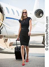 Woman With Luggage Walking Against Private Jet