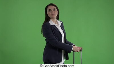 Woman with luggage waving her hand saying hello against green screen