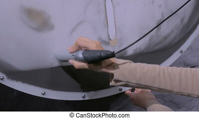 Woman with magnet stick controls ironsand particles -...