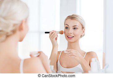 woman with makeup brush and powder at bathroom - beauty,...