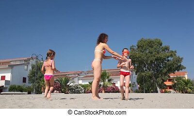 Woman with male and female children play in hide and seek on beach