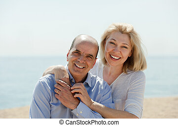 Woman with man together against sea in background