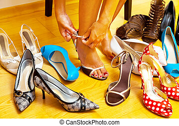 Woman with many shoes to choose from - A young woman has...