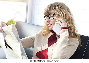 woman with map and mobile phone on the sofa at home