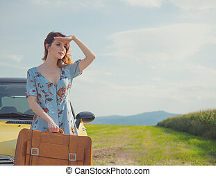 woman with map and suitcase near a yellow car