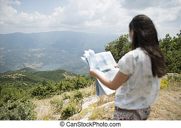 Woman with map high in the mountain