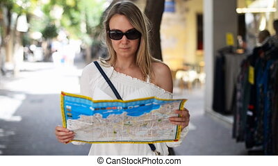 Woman with map in the street.