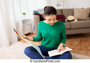 woman with map planning her travel at home