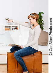 Woman With Map Pointing While Sitting On Suitcase