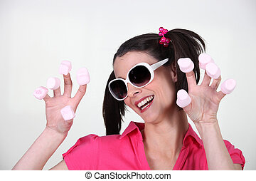 Woman with marshmallows on fingers