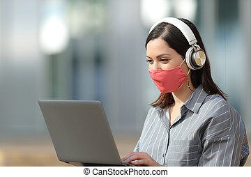 Woman with mask using laptop and headphones in the street