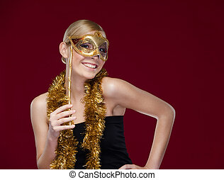 Woman with masquerade mask and tinsel, isolated on purple