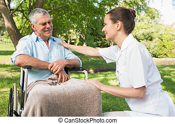 Woman with mature father sitting in wheel chair at park -...