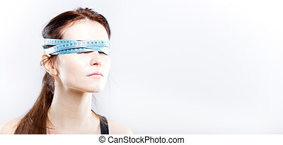 Woman with measuring tape on eyes