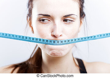 Woman with measuring tape on mouth