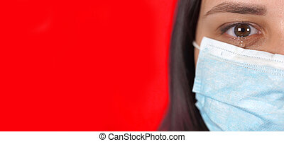 Woman with medical mask on her face. Close-up of woman's crying eye. Concept of coronavirus epidemic or diseases.